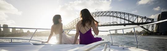 坐在航行於雪梨海港遊艇前部的兩位女士